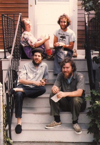 Food Not Bombs co-founders Susan Eaton, Brian Feigenbaum, C.T. Lawrence Butler and Keith McHenry sitting outside their home in Cambridge, Massachusetts in the summer of 1981. Mira Brown, Jessie Constable, Amy Rothstien and Jo Swanson are not pictured.