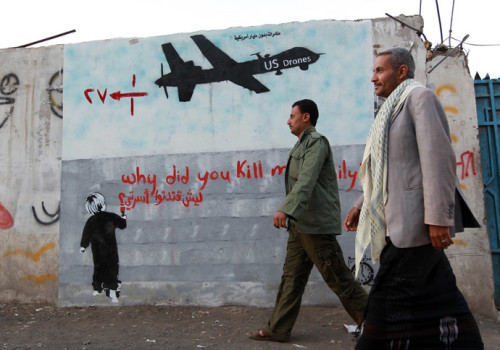 "More than a dozen dead, many more injured. Yemeni men walk past a mural depicting a US drone and reading "" Why did you kill my family"" on December 13, 2013 in the capital Sanaa."