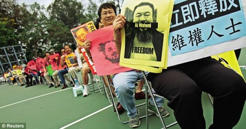Ai Weiwei supporters display posters that show his picture and the word, Freedom