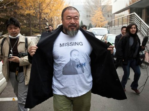 """I once was lost, but now I'm found."" Chinese dissident artist Ai Weiwei opens his jacket to reveal a shirt bearing his portrait as he walks into the Beijing Local Taxation Bureau."
